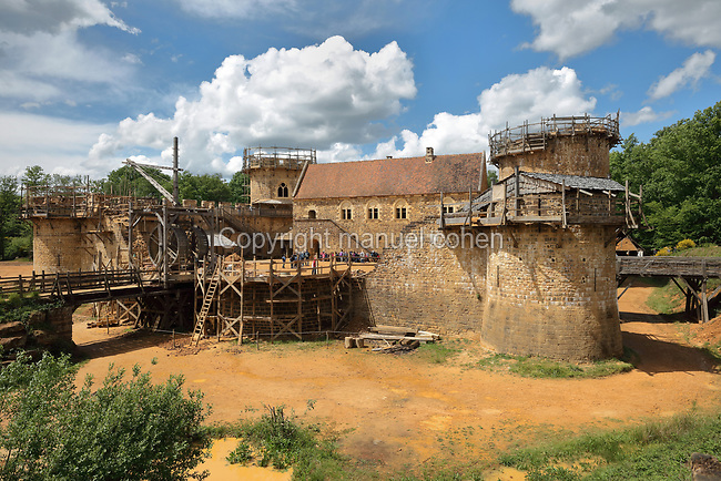 North Range or Logis Seigneurial in the centre, completed 2010, with Corner Towers to the left and right, still under construction, lifting gear or squirrel cage with double drum, and footbridges over the moat trench, at the Chateau de Guedelon, a castle built since 1997 using only medieval materials and processes, photographed in 2017, in Treigny, Yonne, Burgundy, France. The Guedelon project was begun in 1997 by Michel Guyot, owner of the nearby Chateau de Saint-Fargeau, with architect Jacques Moulin. It is an educational and scientific project with the aim of understanding medieval building techniques and the chateau should be completed in the 2020s. Picture by Manuel Cohen