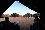 Foreign workers sit inside a tent at a temporary shelter at the Tunisia-Libya border near Ben Guerdane, Tunisia, Friday, Feb. 25, 2011. Thousands crossed the border into Tunisia, fleeing the violence of an uprising in Libya. Opposition forces reportedly have control of much of the country, but Col. Muammar Qaddafi still controls the capital Tripoli.