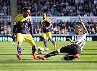 Pictured L-R: Jonathan de Guzman of Swansea is tackled by Mathieu Debuchy of Newcastle. Saturday 19 April 2014<br /> Re: Barclay's Premier League, Newcastle United v Swansea City FC at St James Park, Newcastle, UK.