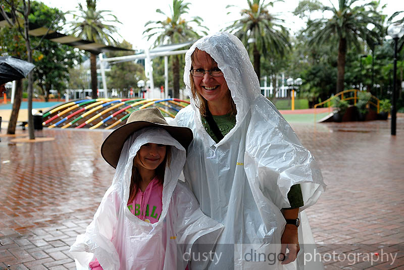 Mother and daughter (6 years old) don plastic raincoats. Darling Harbour, Sydney, Australia