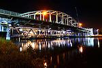 NIEUWEGEIN -  In het holst van de nacht heeft Rijkswaterstaat een tijdelijke hulpbrug vanaf een ponton op de plaats van de weggeschoven Jutphasebrug over het Amsterdam-Rijnkanaal getakeld. De uit 1936 daterende boogbrug krijgt door bouwcombinatie KWS-Mercon een opknapbeurt en is een avond eerder op hoge hulppijlers verschoven waar later de stalen constructie versterkt, brugdek en pijlers gerepareerd en de brug opnieuw geverfd wordt. De Jutphasebrug zal naar een ontwerp van ingenieursbureau Movares volgend jaar 45 cm hoger worden teruggeschoven om containervaart onder de brug te vereenvoudigen. De renovatie van de Jutphasebrug is onderdeel van het project KARGO(Kunstwerken Amsterdam-Rijnkanaal Groot Onderhoud) waarbij acht stalen bruggen over het Amsterdam-Rijnkanaal, Lekkanaal en Buiten-IJ worden gerenoveerd en verhoogd. COPYRIGHT TON BORSBOOM
