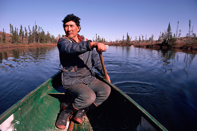 Cree Trapper, Abel Brien paddles his canoe while out hunting in the autumn. Quebec, Canada.