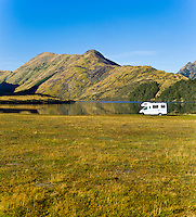 Caravan Parked at Lake Moke Department of Conservation Campsite (DOC Campsite), Queenstown, South Island, New Zealand. Lake Moke, 10km from Queenstown is both a stunning lake and a department of conservation campsite (DOC campsite) with access for both caravans and campervans. In the early mornings Lake Moke is often perfectly still providing picture perfect reflections of the surrounding hills and mountains in the water. The combination of a fabulous golden hour as the sun rose over the hills, the morning mist lifting from the lake, and the rich, orange, autumn trees made this nights camping at the Lake Moke department of conservation campsite (DOC campsite) particularly special.