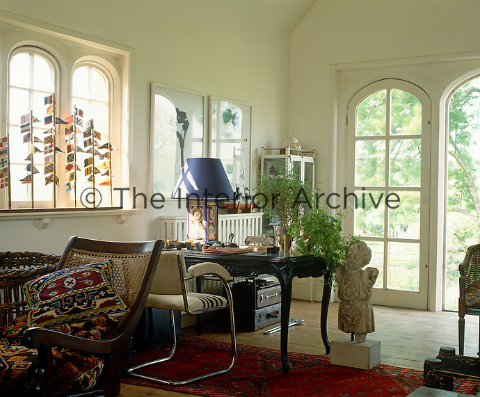 In this home office the desk faces the large French windows with a tranquil view of the garden beyond