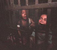 Qi Qi, 3, male (right)  and Gwen Gwen, 5, are kept in a cage in a village house belonging to their uncle. The children's parents are both in prison and the uncle is too poor to afford child care for the children and are afraid they may be stolen a common problem in China...PHOTO BY SINOPIX