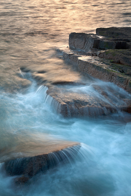 Waves spill over the shoreline rocks at sunset along the Schoodic Peninsula, Acadia National Park, Maine, USA