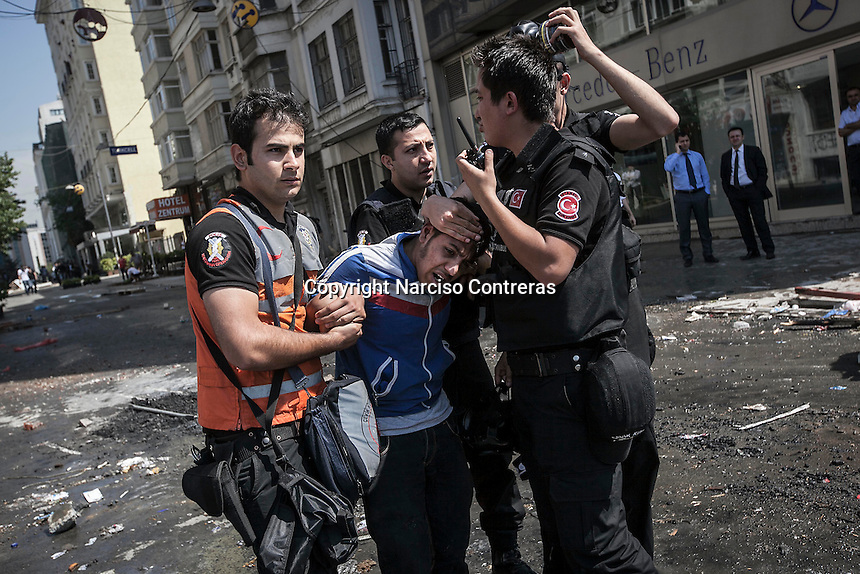 n this Tusday, Jun. 11, 2013 photo, a protester is detained by anti-riot police during clashes at the streets of Taksim Square in Istanbul,Turkey. (Photo/Narciso Contreras).