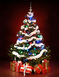 Shining decorated Christmas tree with gifts under it. Isolated on dark red background.