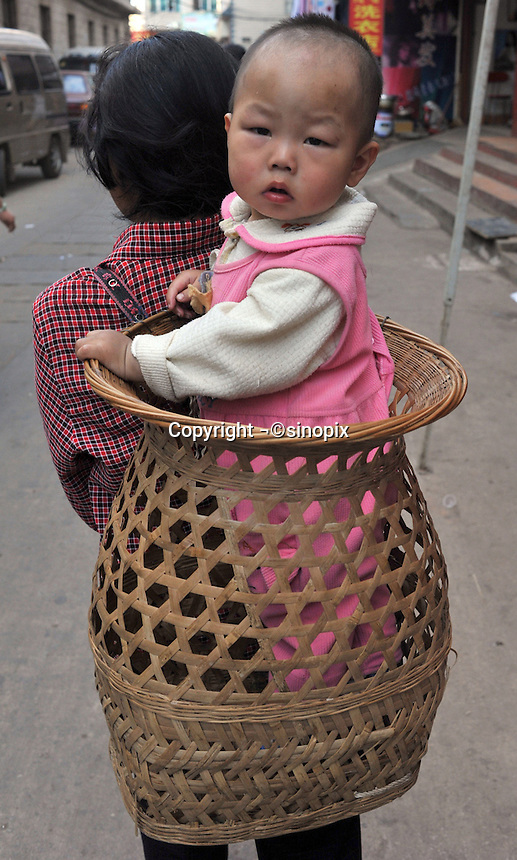 A mother carries her child in a basket in an migrant area known for child abductions in the suburbs of Kunming city.   Girls in China are increasingly targeted and stolen as there is a shortage of wives as the gender imbalance widens with 120 boys for every 100 girls..PHOTO BY SINOPIX
