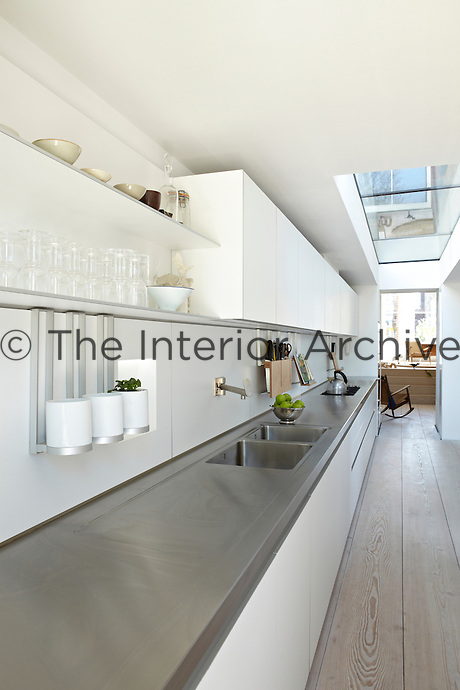 A stylish modern white kitchen with a neutral wood floor and a skylight . Two sinks are set in the grey work surface and glassware is arranged on shelving above. A doorway at the end leads to the living room beyond.