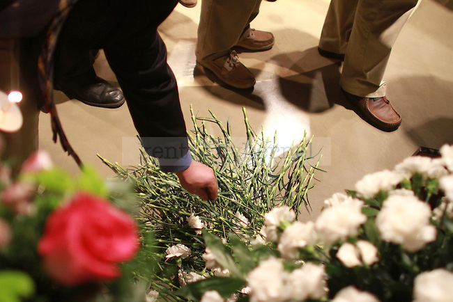 A pile of carnations, the flower for the Delta Sigma Phi fraternity, are placed by members of the Delta Sigma Phi fraternity at the Candlelight Vigil for Alex Ehr in the Newman Center in Lexington, Ky., on 2/23/12. Photo by Brandon Goodwin | Staff