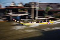 Tourists in long tail boat in canal near Damnoen Saduak Floating Market,.Damnoen Saduak, Thailand