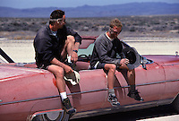 Two men sitting on a dusty cadillac car in the desert near Tonopha, NV.