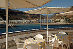 Parasols with the beach and the resort of Mogan, Puerto Mogan, Gran Canaria, Canary Islands, Spain
