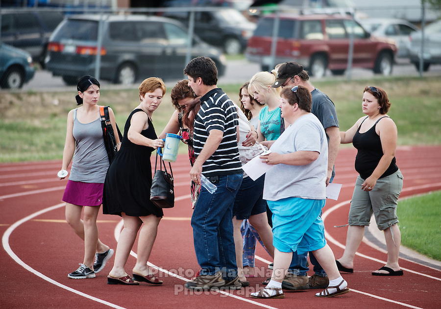 The mother of AJ Boik (cq), who was killed in the shootings at the Aurora Century 16 theater, is helped as she walks away from a vigil held at Gateway High School for her son in Aurora, Colorado, Saturday, July 21, 2012. James Holmes (cq), 24, is suspected in the shooting which occurred during the midnight premiere of the new Dark Knight Batman movie...Photo by MATT NAGER