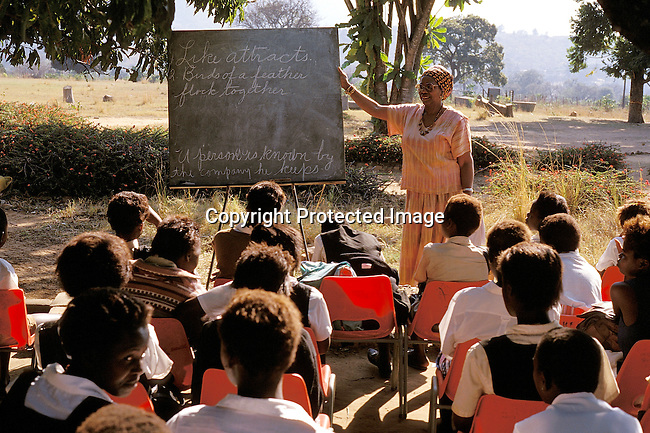 EDPRIMA19112.Education. School. Primary. Mutale. Tshandama Primary School. Ernistene Wilson, 58 years old. Peace corps volunteer. Teaching an outdoor class. She completed a Doctorate in African-American teachers., '97. Class, students, school uniform. Chair..©Per-Anders Pettersson/iAfrika Photos.