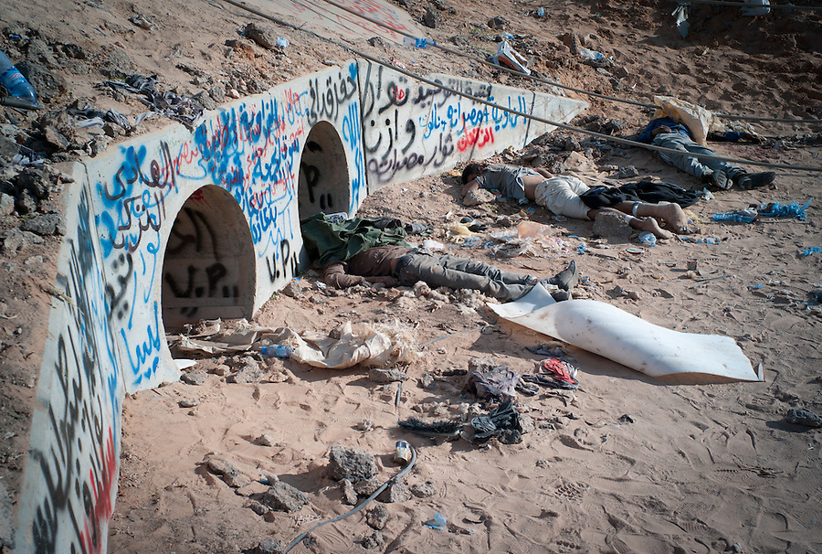 Dead bodies lie in front of the tunnels where Muammar Gaddafi is claimed to have been found in Sirte, Libya, October 20, 2011. The death of Muammar Gaddafi brings closure to an 8 month uprising turned revolutionary war.