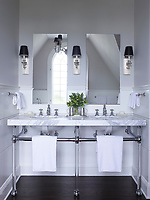 The elegant bathroom is painted in Benjamin Moore's Gray Owl; the two washbasins are set in a marble shelf supported on legs. Wall light flank the mirrors above the basins.