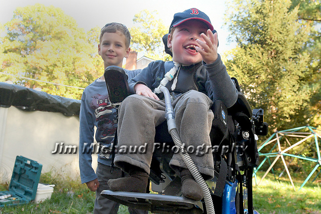 Paul Gramuglia, 6, blows kisses to the construction workers building his Fort Paul, a large playscape in his backyard, as his brother and his best friend Leo, 9, looks on,  as a wish comes true for the 6-year-old who is confined to a wheel chair courtesy of Make-A-Wish,  Friday, Oct. 25, 20107, at their South Windsor home. (Jim Michaud / Journal Inquirer)