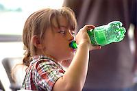 Girl age 7 drinking soda pop at Minneapolis International Airport.  Minneapolis  Minnesota USA