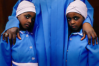Twin girls attend an early morning church service at a Zion church in Site B Khayelitsha, South Africa. (Photo by: Per-Anders Pettersson)