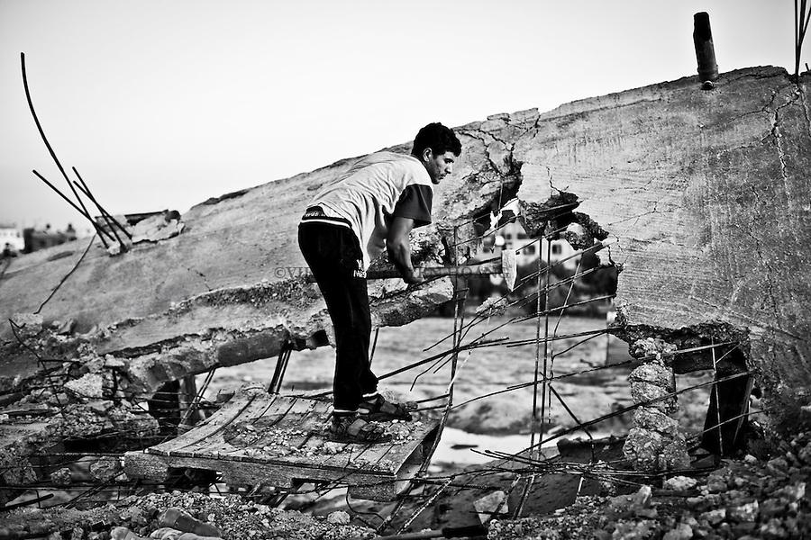 Gaza, Khuzaa: un jeune homme enl&egrave;ve le fer des d&eacute;combres de leurs maisons qui ont &eacute;t&eacute; d&eacute;truites par des bombardements isra&eacute;liens l'&eacute;t&eacute; dernier. Il r&eacute;utilisera ce fer pour la reconstruction de sa maison ou le vendra au march&eacute;. <br /> <br /> Gaza, Khuzaa:Young man is taking away the iron of the rubbles of their houses that have been destroyed by israeli shellings last summer. He will uses this iron to rebuild his house or sell it at the market.