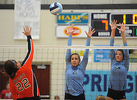 NWA Democrat-Gazette/ANDY SHUPE<br /> Lora Brown (22) of Rogers Heritage sends the ball over the net as Paige Williams (21) and Jaden Williams of Springdale Har-Ber reach to block Thursday, Sept. 17, 2015, at Wildcat Arena in Springdale. Visit nwadg.com/photos to see more photographs from the game.