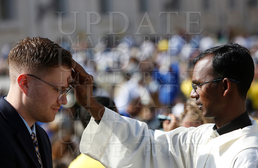 A priest blesses a believer during a Mass celebrated by the Pope for the canonization of the blessed Giovanni Enrico Newman, Giuseppina Vannini, Maria Teresa Chiramel Mankidiyan, Dulce Lopes Pontes and Margarita Bays, in St. Peter's Square at the Vatican, October 19, 2019. UPDATE IMAGES PRESS/Riccardo De Luca <br /> <br /> STRICTLY ONLY FOR EDITORIAL USE