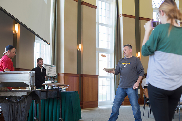 Jim Anderson, of Pittsburgh, catches a pancake from Matt Block, whom makes pancakes for Chris Cakes, while his daughter Maura Anderson, a sophomore, video records it on her phone during the Dad's Weekend Flying Pancake Breakfast on November 6, 2016.