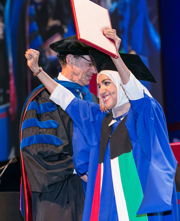 A happy graduate as the Rev. Dennis H. Holtschneider, C.M., president of DePaul University, and Ray Whittington, dean of the Driehaus College of Business, hand out diplomas to the graduates as the Driehaus College of Business held its commencement ceremony Sunday, June 12, 2016, at the Allstate Arena in Rosemont, IL. Nearly 1,400 students received their degrees. (DePaul University/Jamie Moncrief)Paul University/Jamie Moncrief)