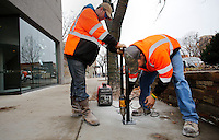 NWA Media/DAVID GOTTSCHALK - 12/3/14 - Luke Kilpatrick, left, a maintenance worker four with the city of Fayetteville Transportation Division, braces a staple style bicycle rack for Aaron Wood, lead maintenance worker, as he bolts the bicycle rack Wednesday December 3, 2014 on the sidewalk on the square in Fayetteville. Twenty one new bicycle racks were installed in the downtown area paid for by benefitting city departments and a city fund specifically designated for bicycle rack installation.