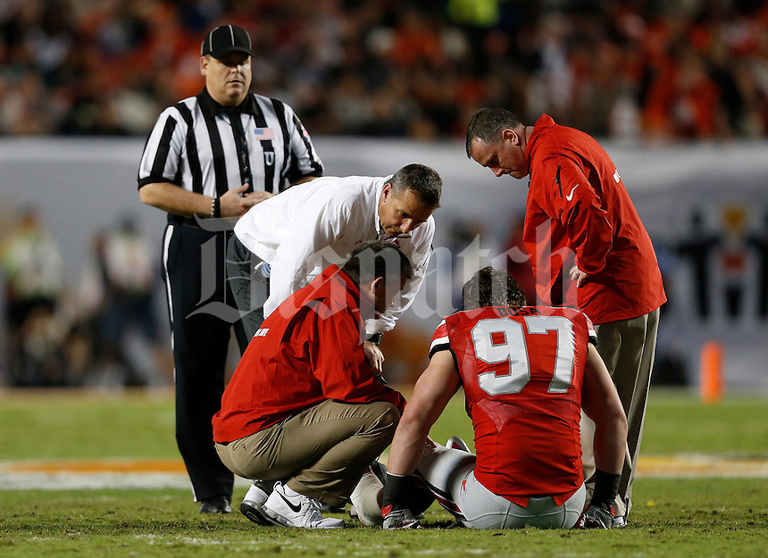 Ohio State Buckeyes head coach Urban Meyer checks on an injured Ohio State Buckeyes defensive lineman Joey Bosa (97) in the second quarter of the Discover Orange Bowl between Ohio State and Clemson at Sun Life Stadium in Miami Gardens, Florida, Friday night, January 3, 2014. As of half time the Ohio State Buckeyes led the Clemson Tigers 22 - 20.(The Columbus Dispatch / Eamon Queeney)
