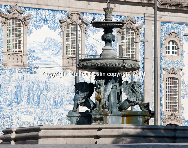 Fountain in the plaza in front of the Carmo Church in Porto, Portugal. The fountain in the plaza by the Carmo Church with its blue and white tiled wall in the background in Porto, Portugal.