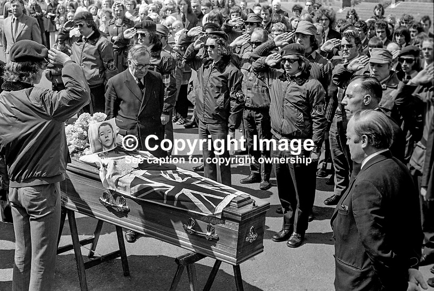 Funeral of UDA member Michael Wilson who was shot by gunmen on 19th June 1973. Michael Wilson lived in the home of his brother-in-law UDA Vice Chairman, Tommy Herron. Herron is married to Wilson's sister. Before the funeral cortege moves off UDA members in para-military gear salute his coffin. For more information re this killing go page 368 of Lost Lives, a detailed listing of deaths during the N Ireland Troubles. 197306190449a.<br />