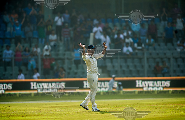 Sachin Tendulkar waves at spectators while fielding at his 200th (and last) test cricket match before his retirement at Wankhede Stadium in Mumbai.