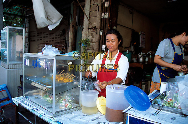 Lady selling food outside a restaurant, Phitsanulok, Thailand
