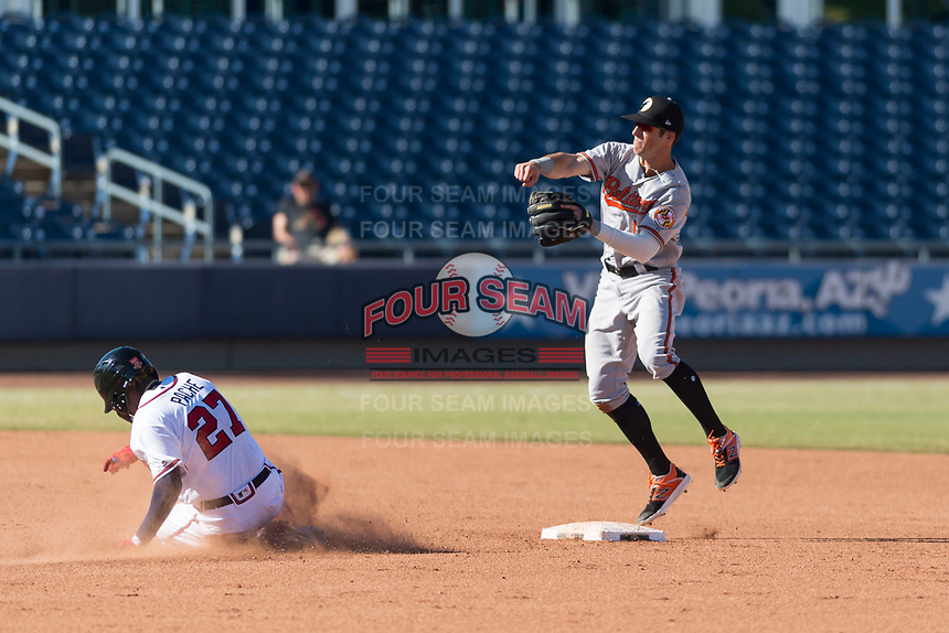 Glendale Desert Dogs second baseman Steve Wilkerson (12), of the Baltimore Orioles organization, throws to first base over Cristian Pache (27) for a game-ending double play during an Arizona Fall League game against the Peoria Javelinas at Peoria Sports Complex on October 22, 2018 in Peoria, Arizona. Glendale defeated Peoria 6-2. (Zachary Lucy/Four Seam Images)
