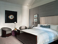 The bedroom is furnished with a custom made sleigh bed in one of the classic Bentley burled wood veneers and a pair of matching Art Deco style tub chairs