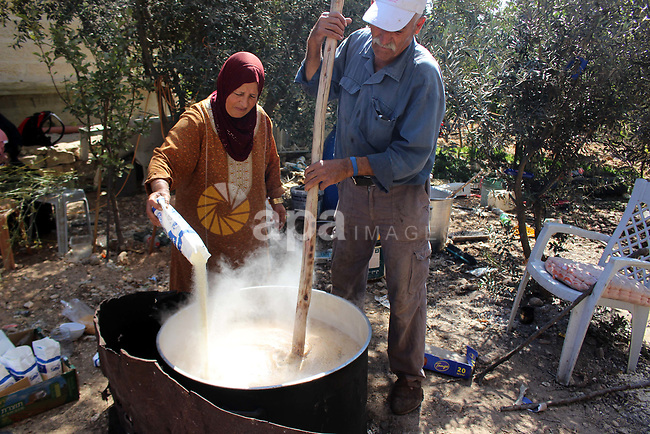 "Palestinians prepare a traditional sweets ""Malban or Turkish delight"" from grape, the West Bank village of Halhul, near Hebron, on September 29, 2019. Hebron is very famous in grape production as it contains many fields of grapes, the summer is the season of harvesting. Photo by Mosab Shawer"