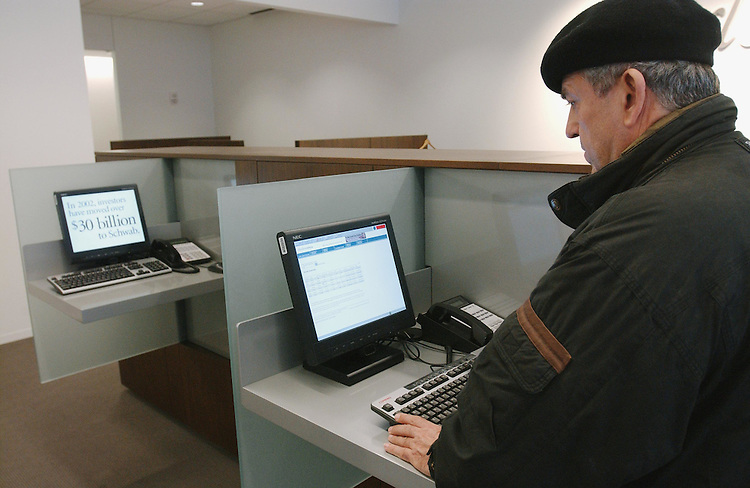 1/28/03.TAXES/INVESTORS--Mustafa Soykan, Ph.D., an Annandale, Va., financial advisor, checks the computer at the K Street branch of Charles Schwab & Co., Inc., in Washington, D.C. Both parties in Congress are creating tax proposals designed to appeal to investors. The centerpiece President Bush's economic plan, a proposal to cut dividend taxes, is aimed squarely at investors. In his State of the Union address tonight, President Bush is widely expected to support more tax breaks aimed at investors, including several proposals by Rob Portman, R-Ohio, and GOP leaders.. CONGRESSIONAL QUARTERLY PHOTO BY SCOTT J. FERRELL