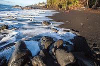 Foamy waves flowing onto rocks and black sand at Kehena Beach, Pahoa, Big Island.
