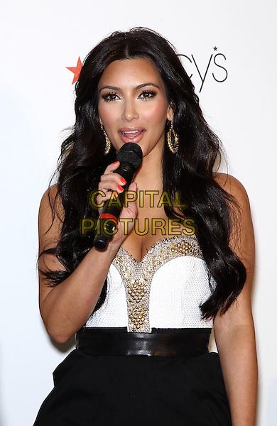 "KIM KARDASHIAN.Macy's welcomes Kim Kardashian to Fashion Show Mall to celebrate her latest fragrance ""Kim Kardashian Gold"", Las Vegas, Nevada, USA, 6th May 2011..half length strapless white bustier top skirt black dress gold microphone  speaking .CAP/ADM/MJT.© MJT/AdMedia/Capital Pictures."