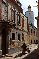 "Low angle view of a narrow street of the old city with a man pushing a cart, Portuguese Fortified city of Mazagan, El Jadida, Morocco, with the pentagonal minaret of the Grand Mosque in the background. El Jadida, previously known as Mazagan (Portuguese: Mazag""o), was seized in 1502 by the Portuguese, and they controlled this city until 1769. Picture by Manuel Cohen"