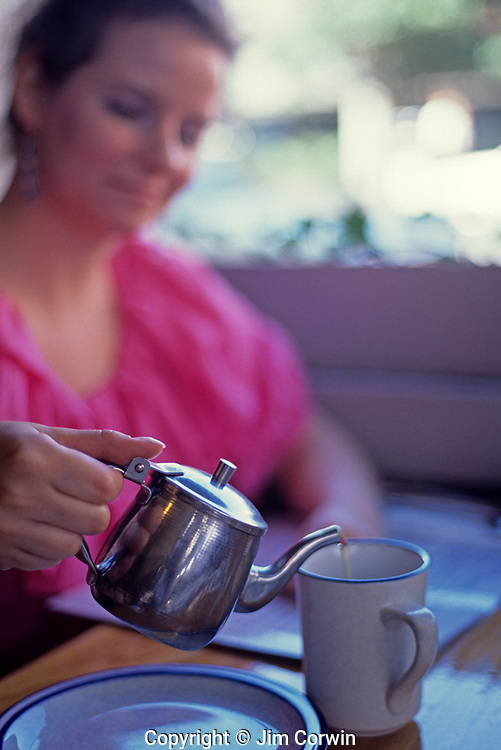 "Woman sitting in cafe pouring  a cup of tea and smiling along the ""Ave"" University District Seattle Washington State USA"