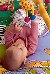 baby boy  3 mos. old on back, closeup, looking at hanging toys, batting at them