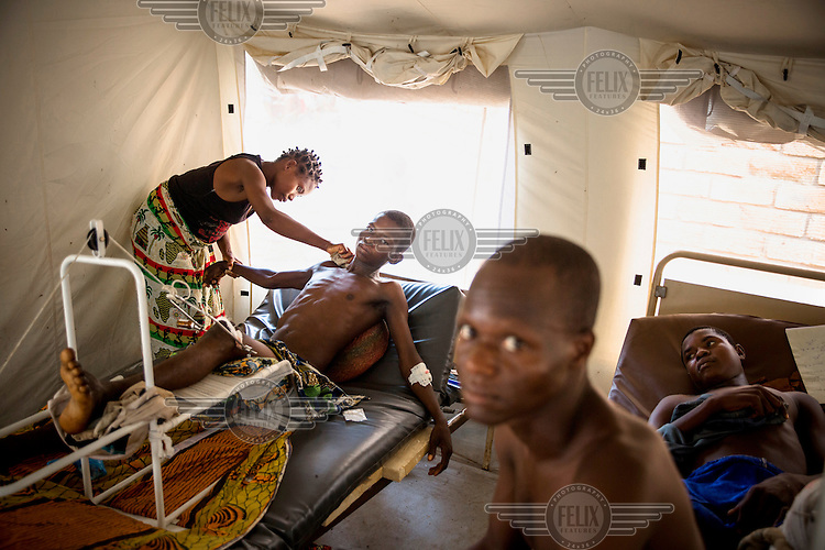 A man wounded during fighting between Christians and Muslims is washed by his wife as he lies in a tent in the community hospital compound. In 2013 a rebellion by a predominantly Muslim rebel group Seleka, led by Michel Djotodia, toppled the government of President Francios Bozize. Djotodia declared that Seleka would be disbanded but as law and order collapsed the ex-Seleka fighters roamed the country committing atrocities against the civilian population. In response a vigillante group, calling themselves Anti-Balaka (Anti-Machete), sought to defend their lives and property but they then began to take reprisals against the Muslim population and the conflict became increasingly sectarian. French and Chadian peacekeeping forces have struggled to contain the situation and the smaller Muslim population began to flee the country.