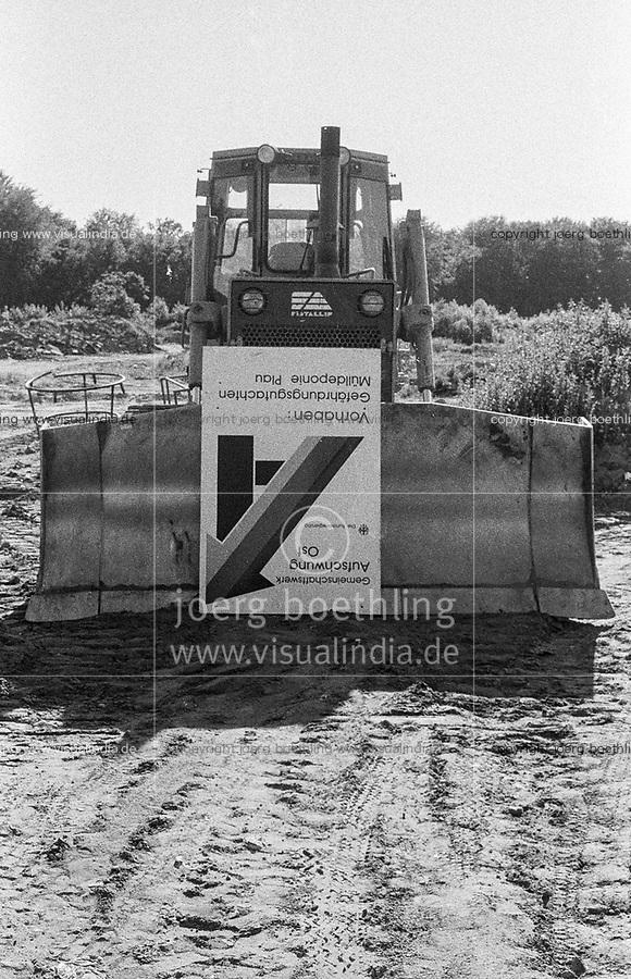 DEUTSCHLAND, Plau, Wiedervereinigung, Raupe mit Schild Aufschwung Ost auf Muelldeponie / former German Democratic Republic, Germany, Plau, caterpillar with signboard upswing East