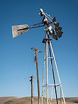 Broken Aermotor windmill on tower, power lines, Salinas Valley, Calif.