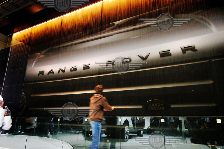 A boy looks at a giant video display behind a wall of water for a Range Rover 4x4 car at the Land Rover stand at the Geneva Motorshow. The company is owned by Indian firm Tata.