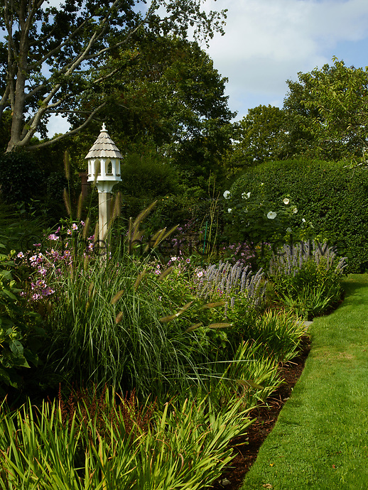 A bird house is set amongst the flower beds and the neatly edged lawn.